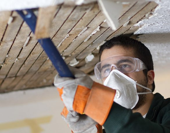 Male Fixing Ceiling man scraping plaster from ceiling lathe. renovation